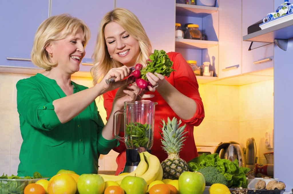 Happy mother and daughter making healthy drink together, smoothie from baby spinach, radishes and fruit